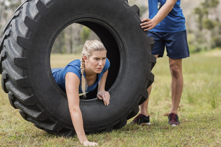 Woman crawling through the tire during obstacle course in boot camp