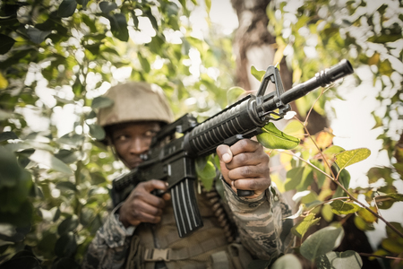 militant: Military soldier guarding with a rifle in boot camp