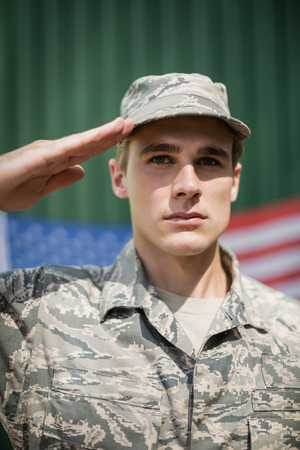 militant: Portrait of military soldier giving salute in boot camp
