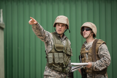 Soldiers showing direction to his colleague in boot camp Stock Photo