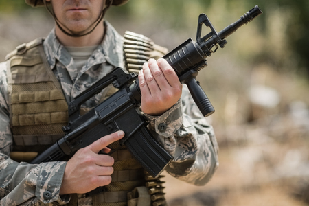 Confident military soldier standing with rifle in boot camp