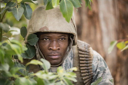 Military soldier hiding behind trees in boot camp Stock Photo