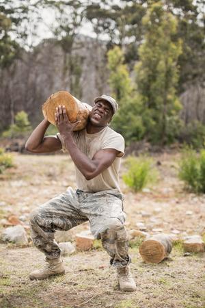 Soldat militaire portant un arbre à creuser pendant le parcours d & # 39 ; obstacles dans le camp de bétail Banque d'images - 75346460