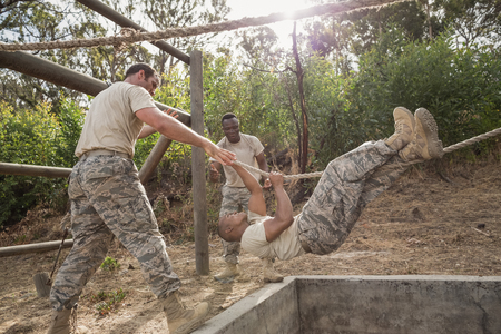 Young military soldiers practicing rope climbing during obstacle course at boot camp Stock Photo