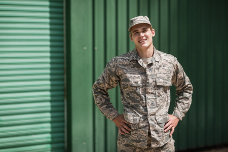 Portrait of smiling military soldier standing with hands on hip in boot camp Stock Photo