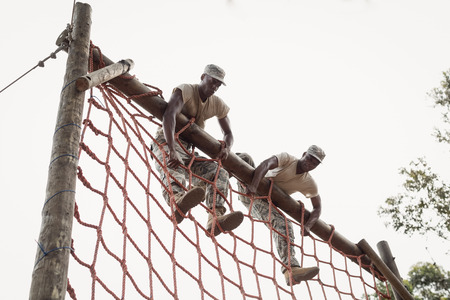 militant: Military soldiers climbing a net during obstacle course in boot camp