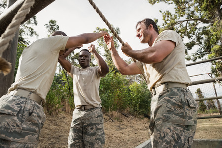 militant: Young military soldiers practicing rope climbing during obstacle course at boot camp