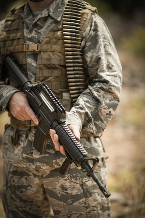 Mid section of military soldier holding a rifle in boot camp