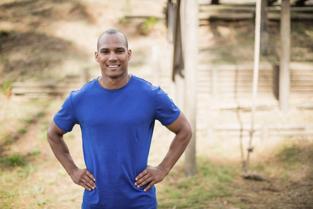 Portrait of fit man standing with hands on hip during obstacle course in boot camp Stock Photo