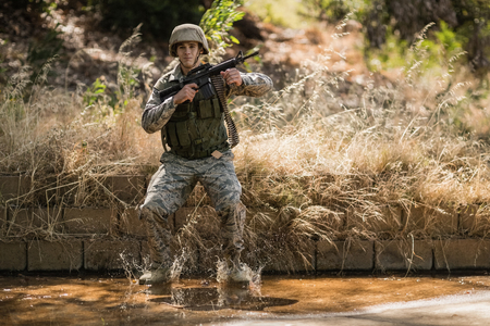 Military soldier with rifle jumping in water in boot camp Stock Photo