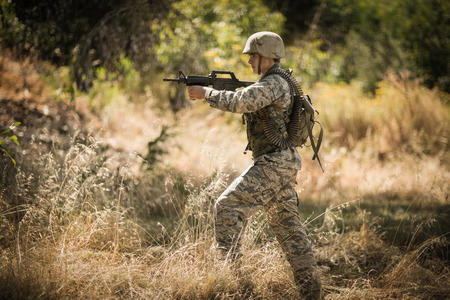 militant: Military soldier aiming with a rifle in boot camp