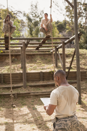 militant: Military soldiers climbing rope during obstacle course training at boot camp