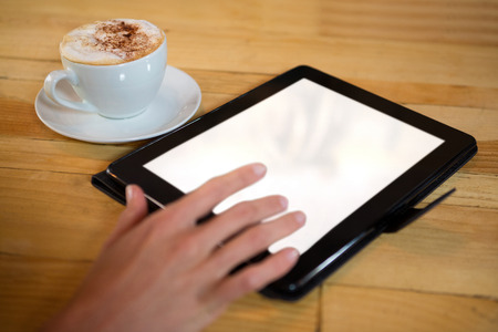 Close-up of woman hand using digital tablet with blank screen by coffee cup in cafe