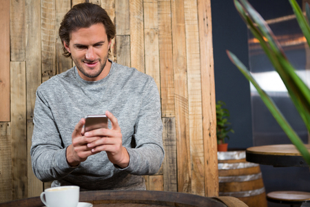 Young man using smart phone at table in coffee shop Stock Photo