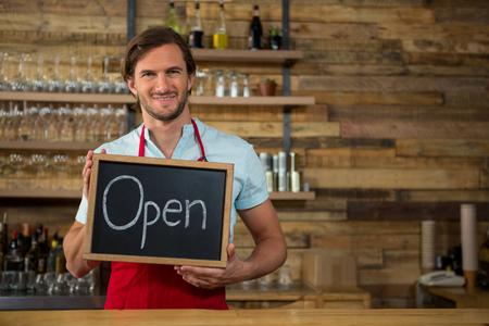 western script: Portrait of happy male barista holding open signboard in coffee shop Stock Photo