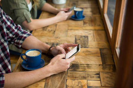Cropped image of man and woman using mobile phones in coffee shop Stock Photo