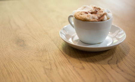 energizing: Close-up of coffee cup with creamy froth on table at cafe