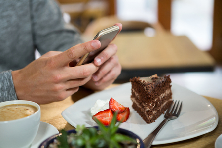 Cropped image of man using mobile phone with coffee and dessert on table in cafe Stock Photo