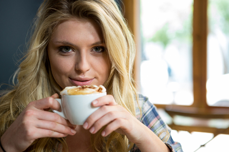 Portrait of beautiful young woman having coffee in cafe