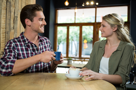 Smiling young couple talking while having coffee at table in cafeteria