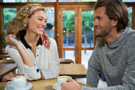 Smiling young couple talking at table in cafeteria