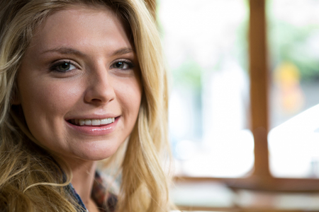 Close-up portrait of beautiful young woman smiling in coffee shop