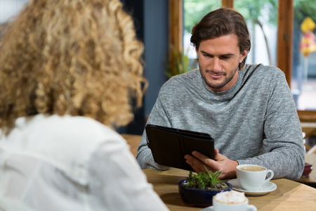 Young man using digital tablet with woman in foreground at coffee house