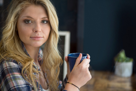 Portrait of beautiful young woman holding coffee cup in cafe