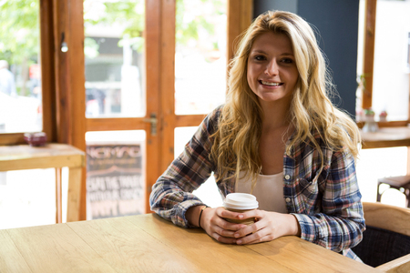 Portrait of smiling young woman holding disposable coffee cup in cafe