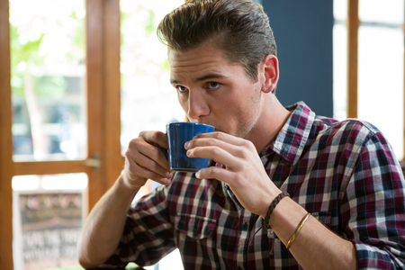 Handsome young man drinking coffee in cafeteria