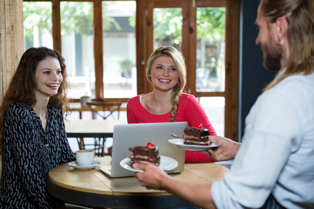 Male barista serving dessert to female customers in coffee shop Stock Photo