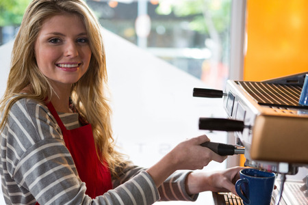 career fair: Portrait of smiling female barista preparing coffee with machine in cafeteria