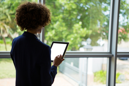company premises: Rear view of businesswoman using digital tablet at conference centre Stock Photo