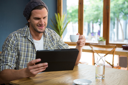 Young man having coffee while holding digital tablet at table in cafe