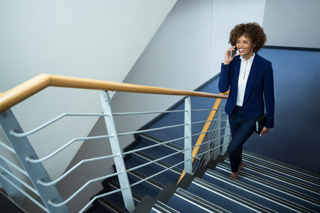 Businesswoman talking on mobile phone while climbing steps at conference centre
