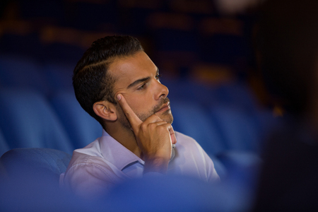 Thoughtful executive listening to speech at conference center Stock Photo