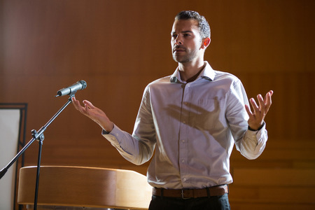 Business executive gesturing while giving a speech at conference center Stock Photo