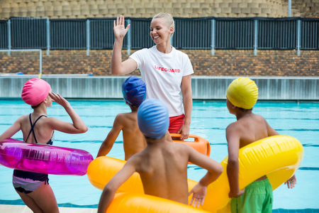 Cheerful lifeguard instructing children at poolside