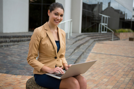 Portrait of smiling businesswoman using laptop in the office premises Stock Photo