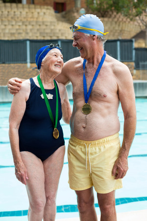 Happy senior couple wearing medals while standing at poolside