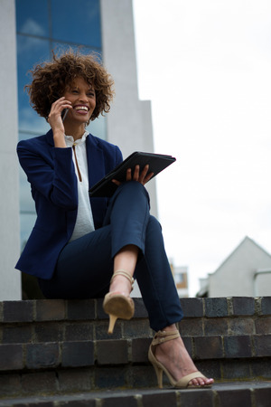 Businesswoman talking on mobile phone near office building