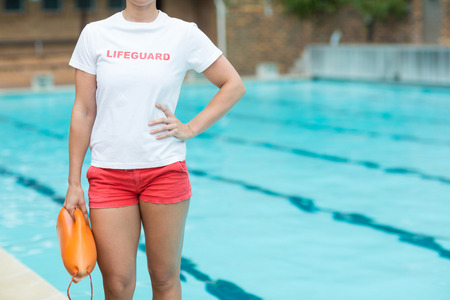 career timing: Mid section of female lifeguard holding rescue can at poolside
