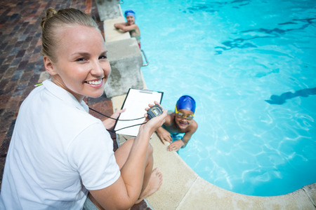 Portrait of female instructor monitoring time of children swimming in pool Stock Photo