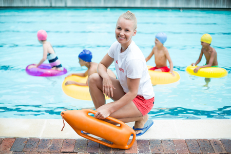 Portrait of female lifeguard holding rescue can while children swimming in pool 스톡 콘텐츠