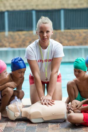 niño sin camisa: Portrait of female lifeguard demonstrating children during rescue training Foto de archivo