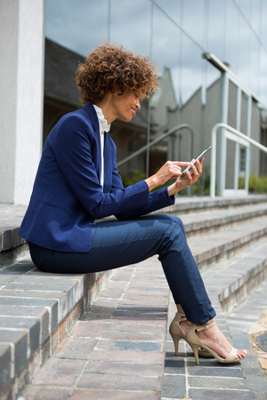 Businesswoman using mobile phone in the office premises Stock Photo