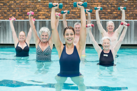 Portrait of trainer with senior swimmers lifting dumbbells in swimming pool
