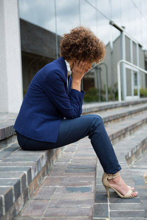premises: Depressed businesswoman sitting in the office premises