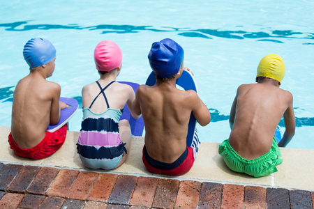 Rear view of girls and boys sitting at poolside Stock Photo