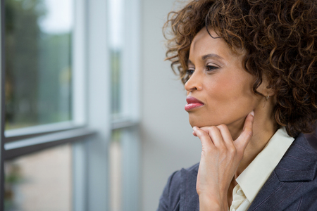 Thoughtful businesswoman looking through window in the office Stock Photo